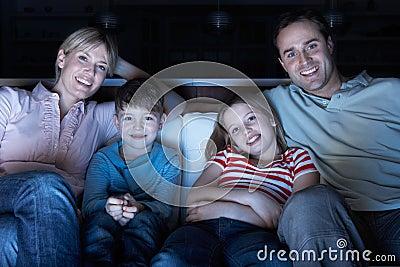 Família que presta atenção à tevê no sofá junto