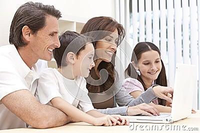 Família que senta-se usando o computador portátil em casa