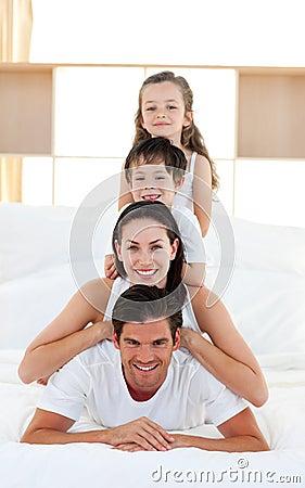 Família que tem o divertimento na cama do pai