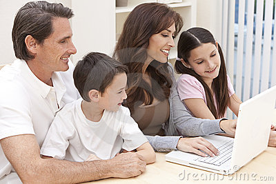 Família que tem o divertimento usando o computador portátil em casa