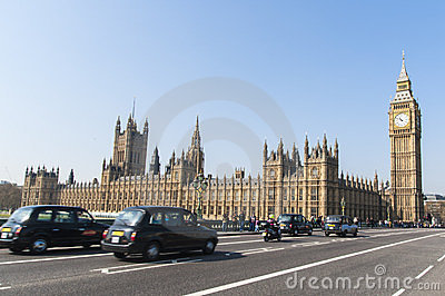 Famous black cab driving by Houses of Parliament Editorial Photography
