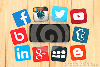 Famous social media icons placed around iPhone on wooden background Editorial Stock Photo