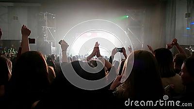 Fans en concierto vivo, muchedumbre de gente iluminada por las luces coloridas, aplaudiendo con las manos para arriba metrajes