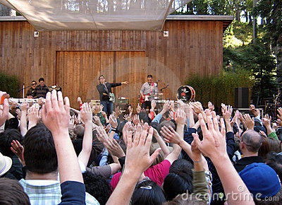 Fans raise hands at concert by They Might Be Giant Editorial Stock Photo