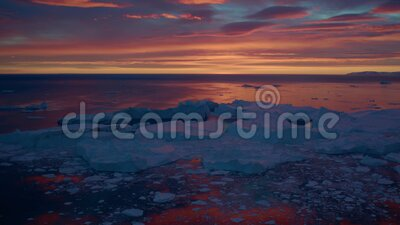 Fantastisk grönland i midnatt som flyger längs stranden av den oändliga kalla horisonten orange moln sky lager videofilmer