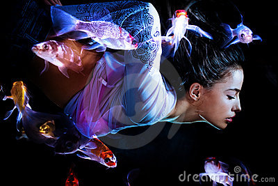 Fantasy woman diving with fishes Stock Photo