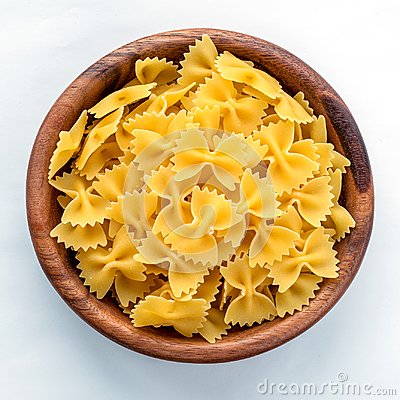 Free Farfalle Macaroni Pasta In Wooden Bowl On White Isolated Background In The Center Close-up With Top. Royalty Free Stock Photos - 114291188