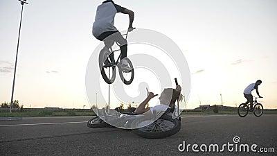 Farligt hopp som utförs av den erfarna kalla cyklisten över hans avkopplade vän som ner sitter med hans cykel i ultrarapid - lager videofilmer