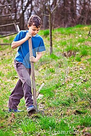 Farm boy digging with a shovel