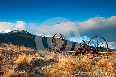 Farm implement and mountains snow