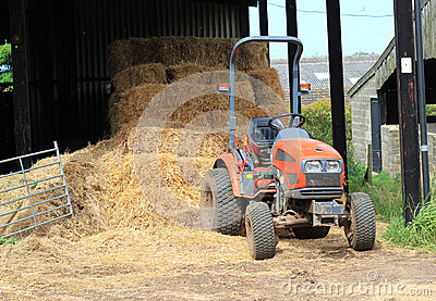 Farm tractor and straw bales.