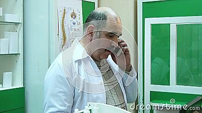 Farmac?utico superior que fala no telefone celular ao verificar a prescri??o na farm?cia video estoque
