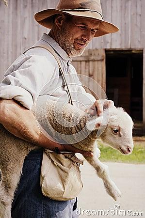 Free Farmer Holding Baby Lamb Stock Photo - 71058740