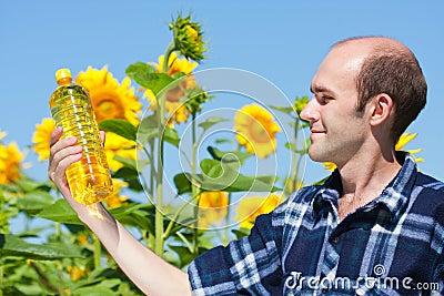 Farmer holding bottle of sunflowers oil Stock Photo