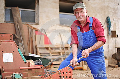 Farmer repairing his red tractor