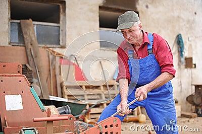 Farmer repairing his red tractor