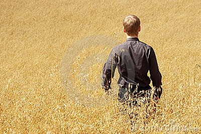 Farmer in suit standing in field of oats