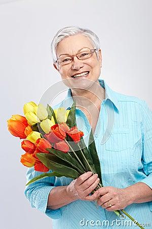 Farmor med att le för blommor