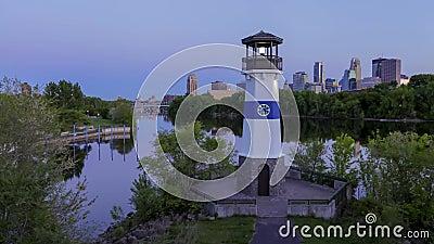 Faro de la isla del horizonte y del auge de Minneapolis sobre el río Misisipi y puentes en el día de la oscuridad a la noche 4K metrajes