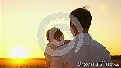 Farsan går med småbarnet i hans armar i afton parkerar i nedgång på solnedgången Farsan och dottern spenderar en fridag tillsamma arkivfilmer