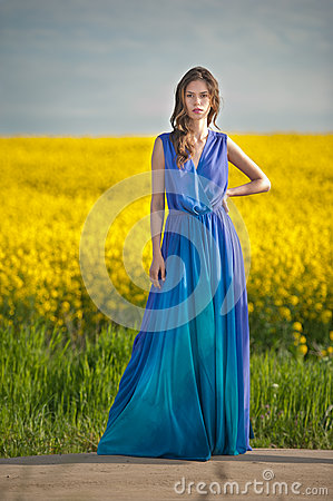 Free Fashion Beautiful Young Woman In Blue Dress Posing Outdoor With Cloudy Dramatic Sky In Background. Attractive Long Hair Brunette Royalty Free Stock Photography - 55088267