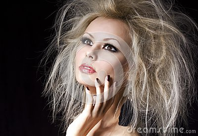 Fashion blonde girl. Beautiful blonde woman with professional makeup and humidity hair style, over black. Vogue model