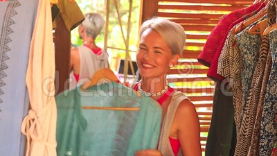Fashion consultant short haircut blonde choose dress at clothing store in Bali tropical shop.  stock video footage