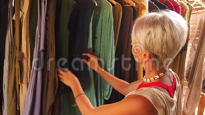 Fashion consultant short haircut blonde choose dress at clothing store in Bali tropical shop.  stock video