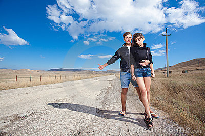 Fashion couple try to stop the car on old road