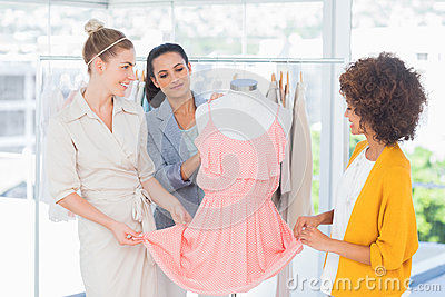 Fashion designers looking at a dress