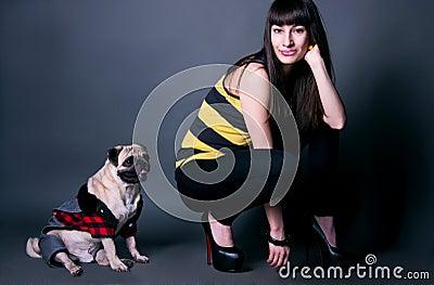 Fashion girl with pug dog in studio
