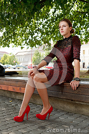 Fashion girl sitting on bench in urban park