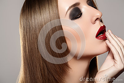 Fashion make-up & cosmetics. Beautiful model with red lips, straight hair