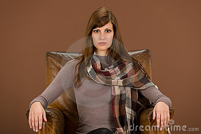 Fashion model on brown leather armchair