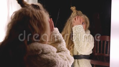 Fashion model with curly hairstyle looking to mirror in dressing room. Beautiful girl in white fur coat posing front. Makeup mirror in fashion studio stock footage