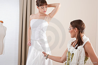 Fashion model fitting wedding dress by designer