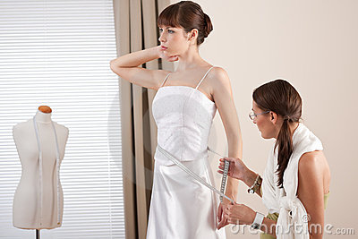 Fashion model fitting white dress by designer