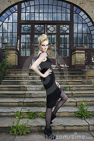 Fashion model in front of and old house