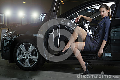 Fashion model posing in a fancy black car