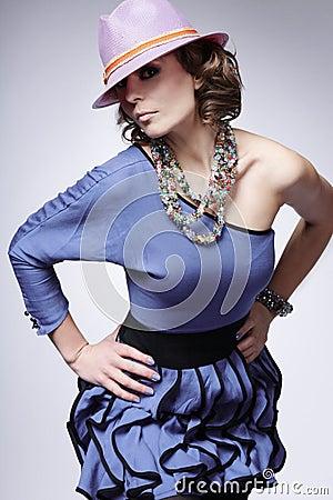 Fashion model posing in studio on gray background.