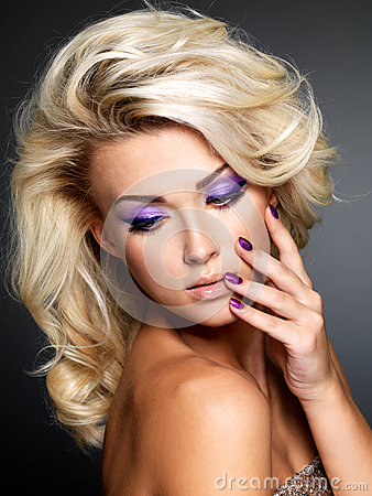 Fashion model with purple manicure and makeup