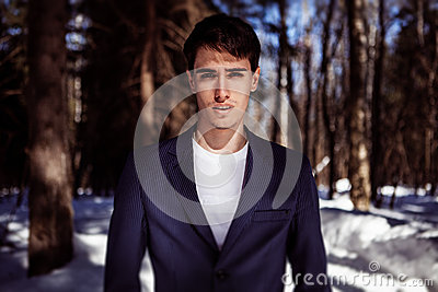 Fashion portrait of a man in snow forest in vogue style