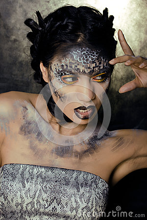 Fashion portrait of pretty young woman with creative make up like a snake