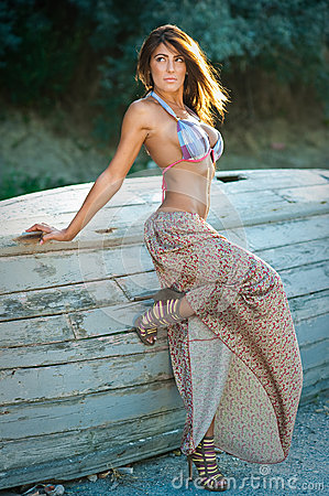 Fashion portrait of  sexy brunette  girl in swimsuit leaning on a wooden boat