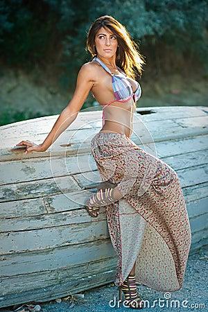Fashion portrait of  brunette  girl in swimsuit leaning on a wooden boat