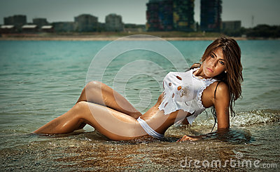 Fashion portrait of young sexy brunette girl in bikini and wet t-shirt at the beach