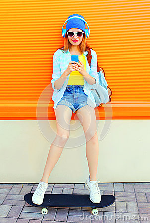 Free Fashion Pretty Cool Girl Is Listens To Music And Using A Smartphone Sits On A Skateboard Over Colorful Orange Royalty Free Stock Photos - 90888888
