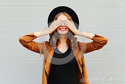 Fashion pretty cool young woman closes eyes cute smiling wearing a vintage elegant hat brown jacket playing having fun Stock Photo
