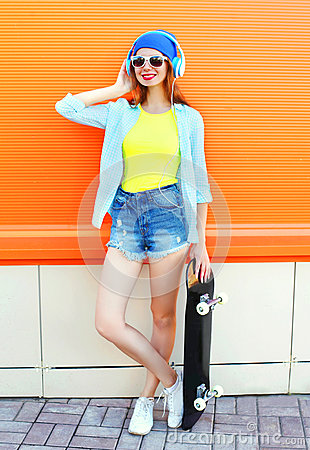 Free Fashion Pretty Woman With A Skateboard In The City Over Orange Colorful Royalty Free Stock Image - 90888976