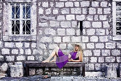 Fashion shot of elegant woman near stone wall